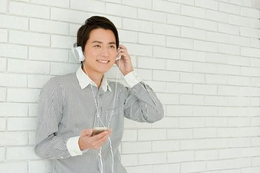 日本人 男性 男 20代 若い ファッション カジュアル インフォーマル 仕事 オフィス 会社 クリエイター デザイナー グラフィックデザイナー webデザイナー シャツ ストライプ 携帯電話 携帯電話を見ている 営業 爽やか 爽快 笑顔 にこやか イヤホン イヤフォン ヘッドホン ヘッドフォン 音楽を聴いている スマホ スマートフォン 音楽 リラックス mdjm024