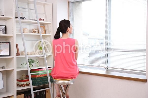 窓際で椅子に座る女性4の写真