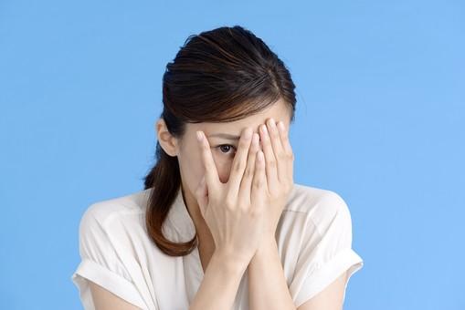 女性 ポーズ 人物 30代 日本人 黒髪 爽やか カジュアル 屋内 正面 上半身 ブルーバック 青背景 半そで 白  両手 顔 覆う 隙間 覗く 好奇心 怖い 恐怖 怖いもの見たさ 片目 右目 見る mdjf013