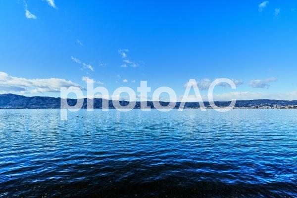 青空を反射した深い青の諏訪湖の写真
