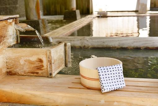 温泉施設 公衆浴場 宿泊施設 ホテル 旅館 温泉 道具 容器 桶 おけ オケ 浴槽 手ぬぐい 湯 お湯 流れる 露天風呂 屋外 外 豆絞り 水辺 縁 木 木材 水流 流れ 小物 和風 木 木材 水流 流れ 小物 和風