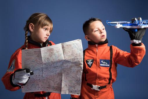 背景 ダーク ネイビー 紺 子ども こども 子供 2人 ふたり 二人 男 男児 男の子 女 女児 女の子 児童 宇宙服 宇宙 服 スペース スペースシャトル 宇宙飛行士 飛行士 オレンジ 希望 夢 将来 未来 体験 職業体験 職業 小道具 小物 ヘルメット 抱える 調べる 調査 地図 道 距離 目的地 おもちゃ ラジコン 外国人  mdmk009 mdfk045