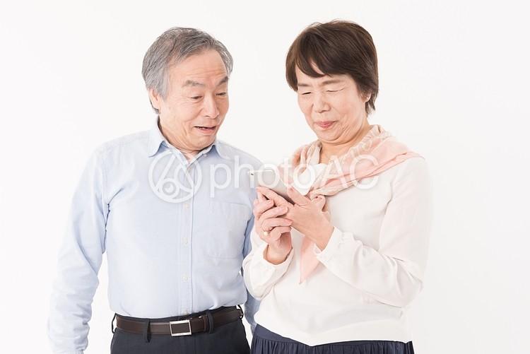スマホを見て微笑む高齢夫婦の写真