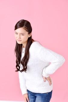 若者 若い 人物 日本人 20代 女性 屋内 ポーズ カジュアル 私服 上半身 ロングヘア かわいい 疲れ 体調不良 疲労 腰痛 ぎっくり腰 痛い おすすめ ピンク 背景 セーター スタジオ撮影 ピンクバック アジア人 ニット ラフ 腰 美人 mdjf007