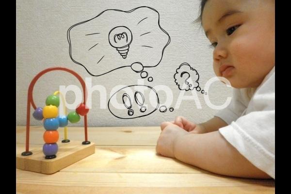 おもちゃを見て考える赤ちゃん2の写真
