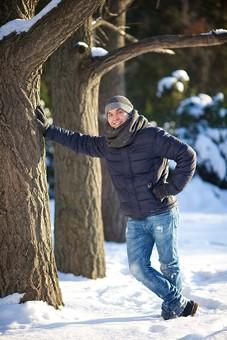 外国人 20代 若い 男性 男 全身 屋外 冬 ウィンター 雪 スノー 笑う 笑顔 スマイル ポーズ 足を組む 腰に手を当てる 木に手を着く 寄りかかる 凭れる 凭れかかる 背景 森 森林 木 積雪 雪景色 自然 mdfm038