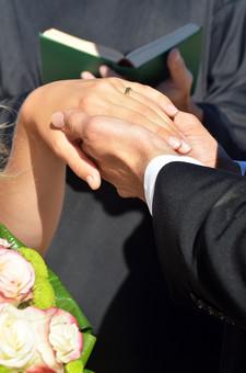 人物 外国人 新郎 新婦 花婿 花嫁 男性 女性 男の人 女の人 成人 男女 カップル 新婚 アベック 夫婦 夫 妻 神父 聖書 ポーズ 手を取る 指輪 指輪の交換 マリッジリング 金 儀式 嵌める 手 指 幸せ 結婚式 ブーケ 花束