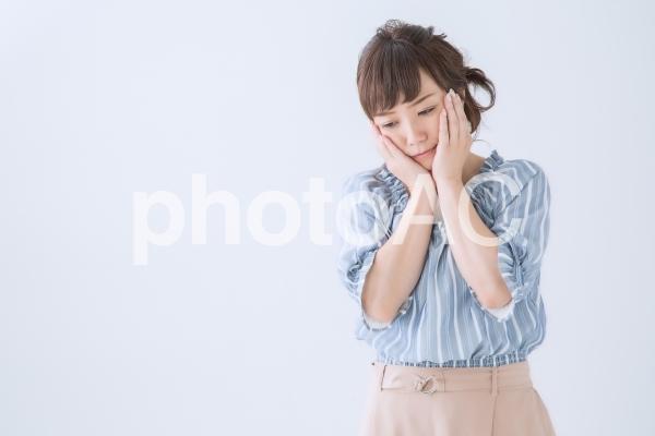 どうしようと考える女性の写真