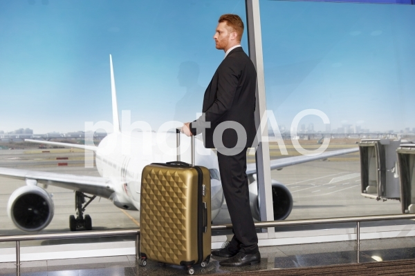 キャリーバッグを引いて飛行機の見える通路にいるビジネスマン1の写真