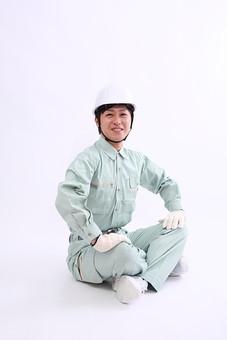 男 男性 若者 20代 仕事 人物 作業員 作業服 職業 工場 工事 工事現場 新入社員 ヘルメット 中小企業 製造業 建設業 建築業 白バック スタジオ あぐら 笑顔 コピースペース 作業着 若い 日本人  全身 mdjm004