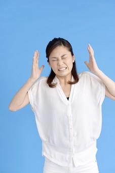 女性 ポーズ 人物 30代 日本人 黒髪 爽やか カジュアル 屋内 正面 ブルーバック 青背景 半そで 白  怒り 怒る  腹立たしい 両手 耳元 上半身 忍耐 耐える 耐え忍ぶ いらいら 聞く耳持たず 聞きたくない うるさい 頭痛 やめて 目 瞑る mdjf013