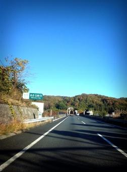 高速道路 秋 ドライブ 紅葉 山 秋晴れ レジャー 旅行 運転 道路 交通 すいている ガラガラ 青空 自然 風景 車 自動車 カーライフ デート お出かけ 引っ越し 標識 雲ひとつない 晴天 晴れ 青 アスファルト トンネル 背景