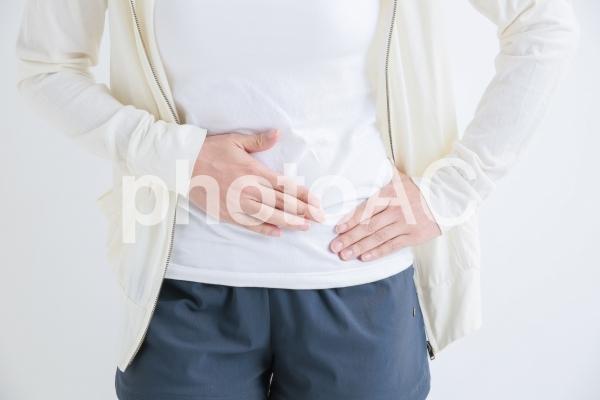 お腹をおさえる女性の写真