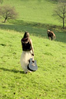 人物 女性 外国人 外人 外国人女性  外人女性 モデル ロングヘア 長髪 黒髪  ファッション フォークロア フォークロア調 ボヘミアン 民族衣装 エキゾチック 幻想 幻想的 ロマンチック ファンタジー  屋外 野外 外 牧場 草原 緑 動物 馬 歩く ギター 後姿 後ろ姿 点景 mdff086