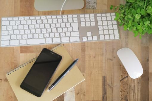 パソコンとスマートフォンの仕事場-茶色の木目デスクの写真