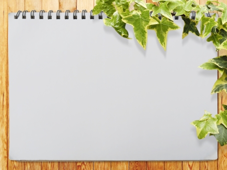 スケッチブックと木目テクスチャと植物背景素材の写真