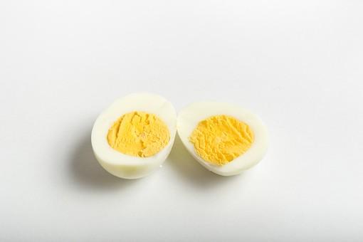 たまご 卵 玉子 タマゴ エッグ 卵色 料理 食べ物 食材 食料 物撮り 屋内 人物なし 上から視線 レシピ 鶏 にわとり ニワトリ ボイル ゆで卵 半分 半割り 黄身 白身 白バック 床 白 黄 2切れ 完熟