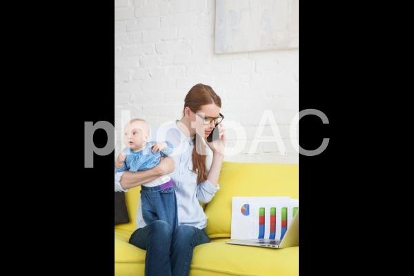 自宅で赤ちゃんを抱っこしながら仕事するお母さん9の写真