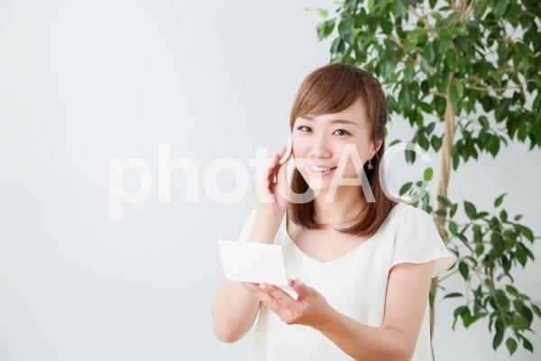 ファンデーションを塗る女性の写真