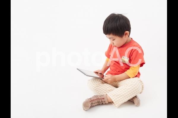 白背景の幼児・タブレット視聴イメージの写真