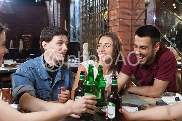 バーで飲む男女の写真