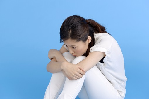 女性 ポーズ 人物 30代 日本人 黒髪 爽やか カジュアル 屋内 横向き ブルーバック 青背景 半そで 白  腕組 全身 苦しい つらい 悲しい 悲痛 悲惨 肩を落とす 悲嘆 嘆く 諦め がっくり 絶望 黒 靴 座る 足 抱える mdjf013