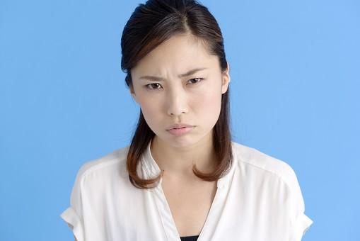 女性 ポーズ 人物 30代 日本人 黒髪 爽やか カジュアル 屋内 正面 ブルーバック 青背景 半そで 白  怒り 怒る 非難 叱る 憤慨 腹立たしい 睨む 睨み付ける 上半身 激怒 凝視 疑い 疑問視 mdjf013