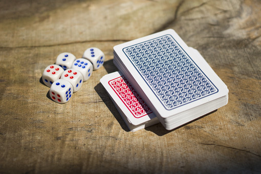 トランプ カード ゲーム 札 娯楽 木 屋外 茶色 机 テーブル 赤 青 束 裏側 裏 サイコロ  木目 手品 マジック 遊び 絵札 乗せる 重ねる 配る 切る カードゲーム