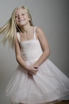 人物 外国人 外人 こども 子供  子ども 女の子 少女 キッズモデル ポートレート  かわいい キュート 無邪気 あどけない 長髪  ロングヘア 金髪 ブロンド ストレートヘア 屋内  スタジオ撮影 ファッション ドレス ワンピース 白 動き モーション アクティブ 髪の毛 スカート 裾 なびく 笑顔 スマイル ポーズ ポートレイト mdfk012