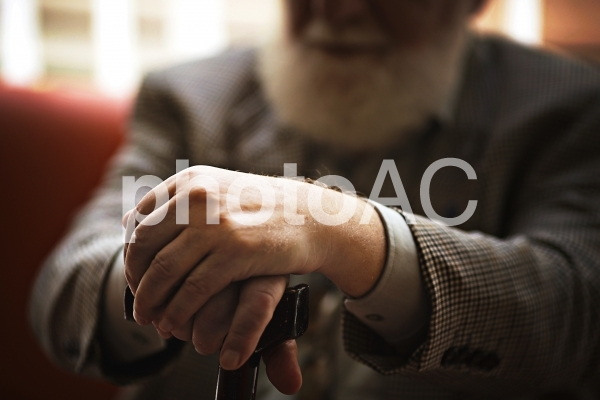 ソファーに座った男性の杖を突いている手元3の写真