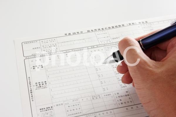 申告書とペンを持った手の写真