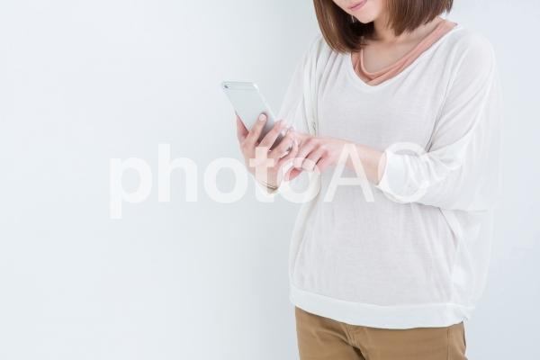 電話を持って考える女性の写真