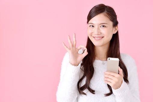 人物 女性 日本人 若者 若い  20代 美人 かわいい ロングヘア カジュアル  ラフ 私服 セーター ニット 屋内  スタジオ撮影 背景 ピンク ピンクバック ポーズ  おすすめ 上半身 スマホ スマートフォン 携帯 電話 OK オーケー サイン 大丈夫 笑顔 mdjf007