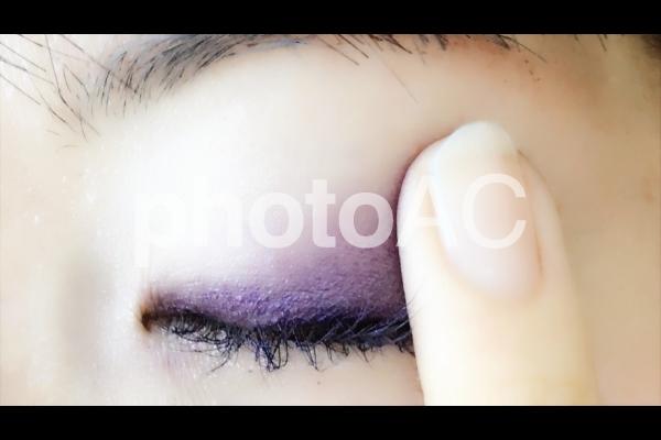 アイシャドウを指で塗る女性の写真