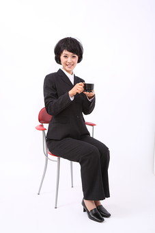 サラリーマン 女 女性 会社員 若者 女子  スーツ 部下 営業 OL 社会人 ビジネス 人物 社員 日本人 20代 仕事 カツラ かつら ウィッグ 笑顔 スマイル  座る 椅子 休憩 一休み コーヒー 珈琲 スタジオ 白バック 白背景 全身 mdjf028