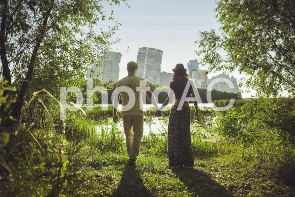 傾いたビル群が見える場所で手をつなぐ男女の写真