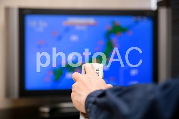 天気予報をテレビで見る男性の写真