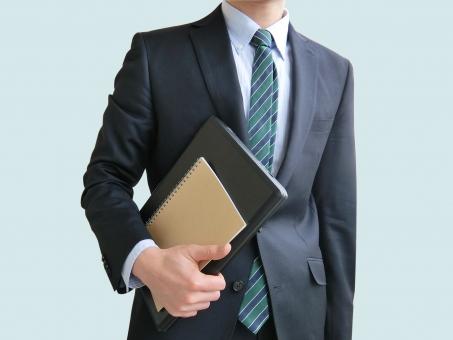 パソコンとノートを持つビジネスマン-青背景の写真