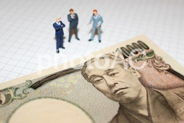 一万円札と考えるビジネスマンの写真
