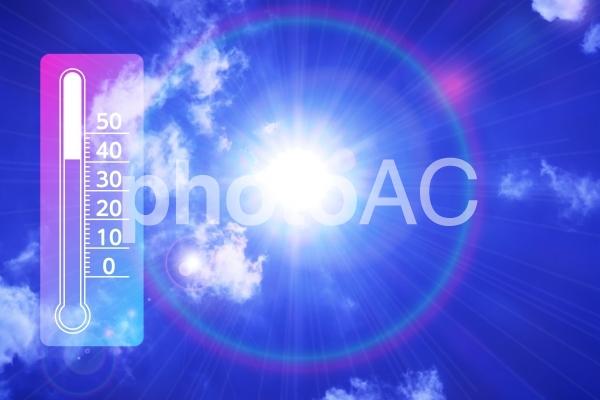 夏の青空とキラキラの太陽プリズム-最高気温の温度計と白い雲の自然風景の写真
