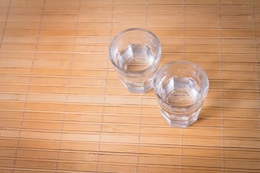 グラス 飲物 容器 透明 クリア コップ カップ  シンプル モノ撮り テーブル 横 水 ミネラルウォーター 天然水 焼酎 日本酒 お酒 アルコール 語る 2人 2つ 休憩 お冷 語り合う 酌み交わす  物撮り ブツ撮り 室内 屋内
