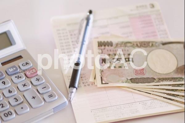 通帳と紙幣と電卓の写真