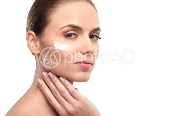 顔にクリームを塗る女性1の写真