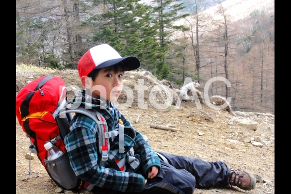 登山中休憩する子どもの写真