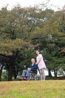 老人 高齢者 お年寄り シニア 男性 男 おとこ  2人 二人  介護士 看護師 エプロン  介護 不自由 椅子 ヘルパー 屋外 緑 木々 木 ジャケット ズボン 青  車いす 車椅子    座る  女性 女 おんな 握る 手 芝生 全身 散歩 外出 mdjf017 mdjms004