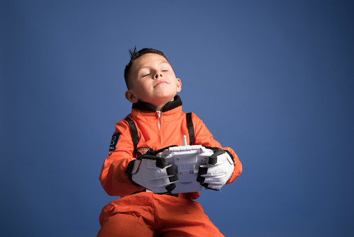 背景 ダーク ネイビー 紺 男の子 男子 男児 男 子ども こども 子供 1人 ひとり 一人 児童 宇宙服 宇宙 服 スペース スペースシャトル 宇宙飛行士 飛行士 オレンジ 希望 夢 将来 未来 体験 職業体験 職業 小道具 小物 おもちゃ コントローラー リモコン コントロール 座る 腰かける 仰け反る のけぞる  外国人 mdmk009