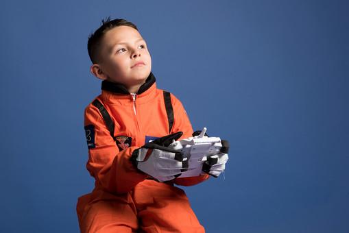 背景 ダーク ネイビー 紺 男の子 男子 男児 男 子ども こども 子供 1人 ひとり 一人 児童 宇宙服 宇宙 服 スペース スペースシャトル 宇宙飛行士 飛行士 オレンジ 希望 夢 将来 未来 体験 職業体験 職業 小道具 小物 おもちゃ コントローラー リモコン コントロール 座る 腰かける 外国人  mdmk009
