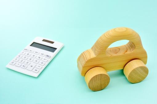 木の車と電卓の写真