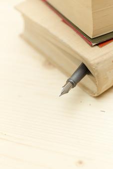 文具 ペン 万年筆 ペン先 ペンポイント グリップ インク ステーショナリー 文房具 小物 筆記 書く 読む 調べる 閉じる はさむ 本 書籍 辞書 ブック 読書 愛用 しおり 書斎 学校 教室 図書館 事務 オフィス 机 テーブル デスク 卓上 接写 室内 屋内