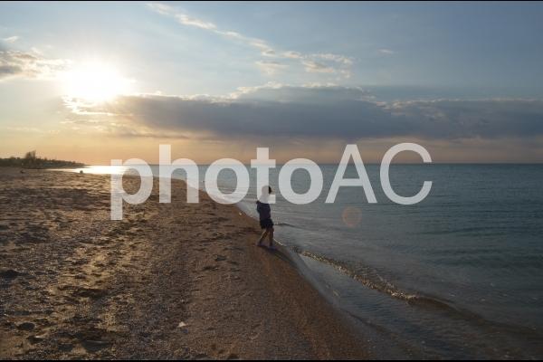 砂浜を歩く少女としずむ太陽の写真